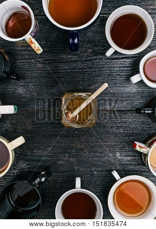 Honey glass jar in the middle of the circle of various tea cups and mugs. Flat lay