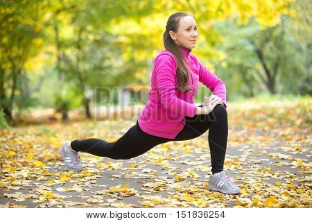 Sporty beautiful happy young woman warming up, stretching before morning running routine, doing high lunges, exercises for legs, hips and buttocks, working out outdoor on autumn day. Full length