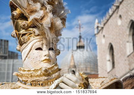 VENICE, ITALY - FEBRUARY 15, 2015: An unidentified person on traditional costume, posing in front of the Doges Palace at Venice Carnival