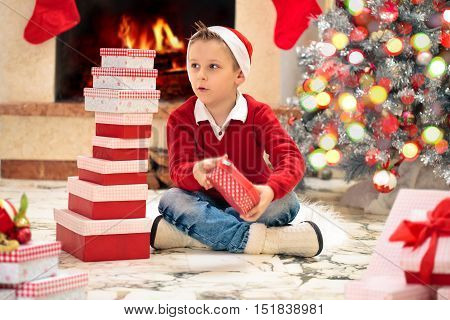 Happy boy near fireplace stacking gifts for Christmas .