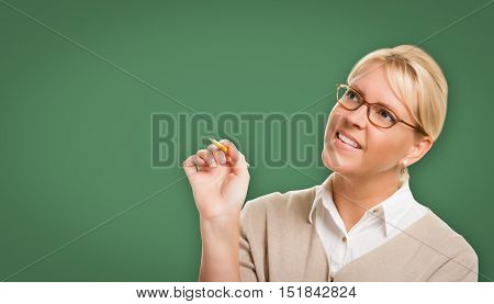 Attractive Young Woman with Pencil and Glasses In Front of Blank Chalk Board.
