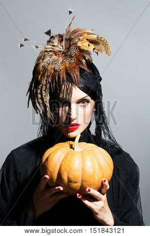 Pretty Sexy Woman In Feather Hat Holds Pumpkin
