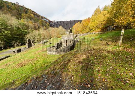 Ruins of Bryntail Lead Mine the Clywedog Dam in the distance. Llanidloes Powys Wales United Kingdom.