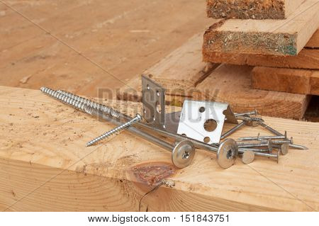 Screws and nails to build a wooden house. Joining wooden beams. Construction works.