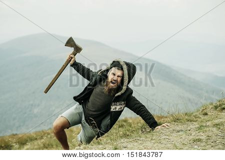 Brutal man lumberjack hipster with long beard and moustache in coat and hood with axe in hand on mountain on foggy sky