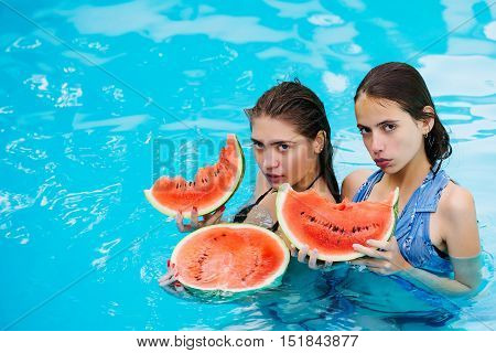 young sexy women or girls with pretty face and wet hair swimming in pool with blue water eating red watermelon sunny summer day outdoor