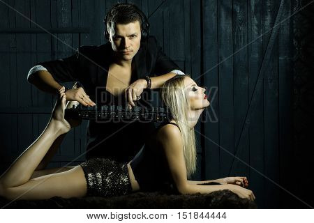 Young man dj in black suit with headset playing music on mixer equipment standing on shoulders and legs of sexy girl blonde in glamour shorts on dark wooden background studio