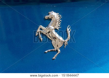 TURIN, ITALY - JUNE 9, 2016: Silver Ferrari prancing horse on a blue car body