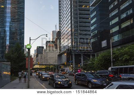 TORONTO,CANADA-AUGUST 2,2015:view of the traffic between skyscrapers in Toronto during a sunset from one of the central street of the city.