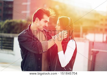 Happy young couple listening music in sunset love and tenderness
