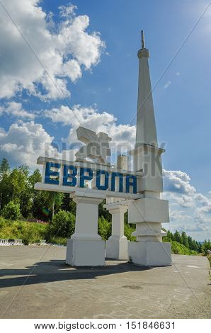 SVERDLOVSK OBLAST RUSSIA - JULY 12 2016: The monument on the border of Europe and Asia on a Sunny summer day. The view from Europe