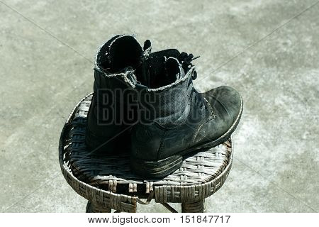 Old boots footwear for work and walking made of black leather and textile with laces on wicker stool on gray background outdoor