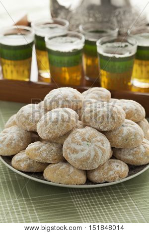Dish with Moroccan festive homemade ghoriba cookies close up and tea