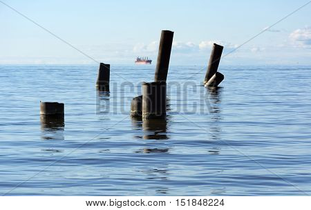 The Gulf of Finland with blue water sea on the horizon sails a ship sticking out of the water pipe stick blue sky Russia