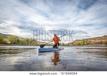 A moment of contemplation - a senior male on stand up paddleboard on a calm mountain lake