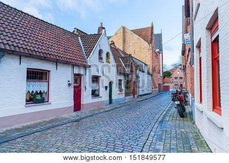 Brugge (Bruges) - February 2016, Belgium: A typical street of Brugge with traditional brick houses and modern motorcycle stands near the wall