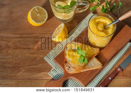 Homemade lemon curd in glass jar with toast on wooden background.
