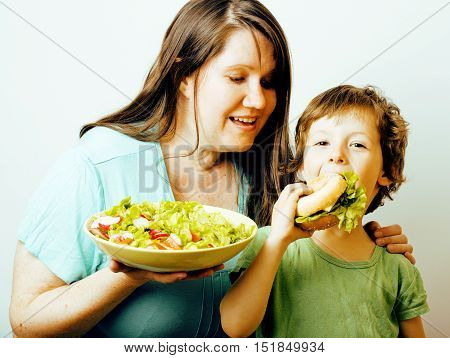 mature woman holding salad and little cute boy with hamburger teasing close up, family unhealthy food