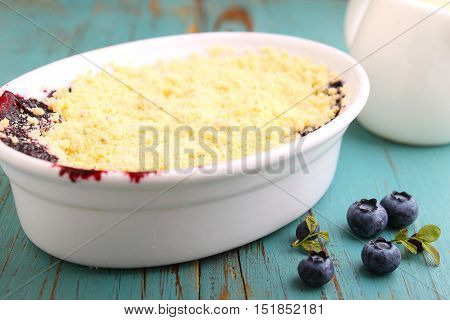 crumble with blueberry bilberry in white plate