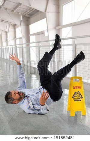 Hispanic businessman falling on wet floor inside office building