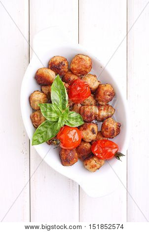 Meatballs with tomato in a white dish on a white background. selective focus.