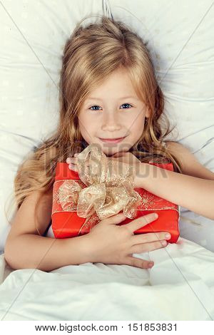 Portrait of happy little girl with a gift in their hands