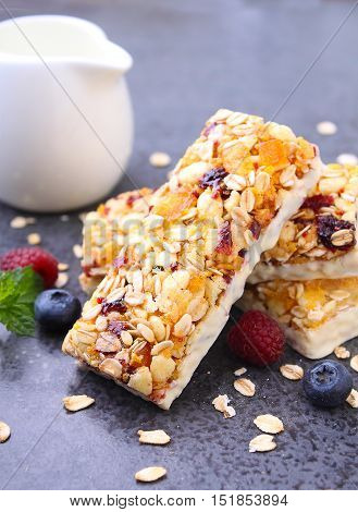healthy snack muesli bars with raisins and dried berries on a black background