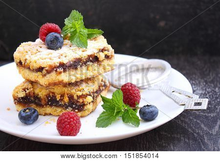 Grated pie on a white plate with raspberry and blueberry on a black background