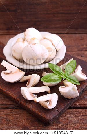 Champignon mushrooms cut into slices on old wooden board