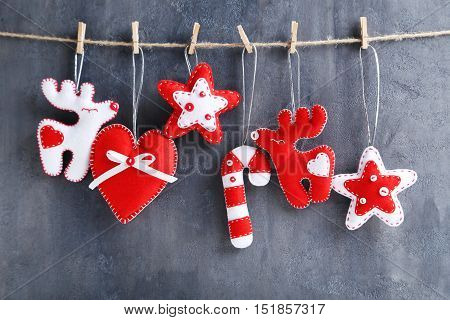 Christmas Decorations Hanging On Rope On Grey Background