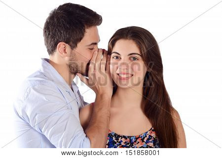 Portrait of a young man whispering secret to his girlfriend. Isolated white background.
