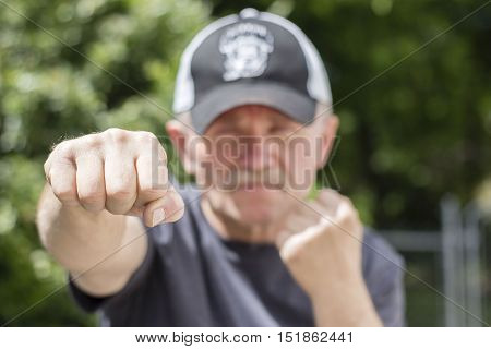 horizontal image of a man from the chest up with his hands in boxing form with his one hand in sharp focus and the rest of image blurred.