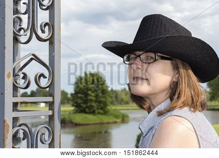 horizontal head shot image of a caucasian middle aged woman wearing glasses with brown shoulder length hair wearing a black cowboy hat with room for text.