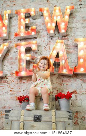 Happy girl smiles, claps and sits near wall with big letters in studio