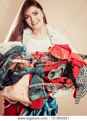 Smiling Girl Hold Pile Of Clothes.