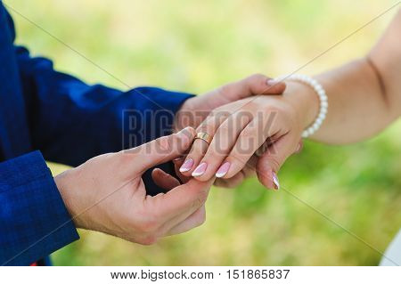 Groom's hand putting a wedding ring on the bride's finger. Meadow, grass in the background, a light green background.