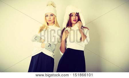 Fashion models people concept. Two women with winter clothes. Blonde and mixed race ladies wearing warm clothing.
