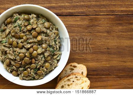 Lentil and parsley spread in bowl with slices of bread on the side photographed overhead with natural light (Selective Focus Focus on the top of the spread)