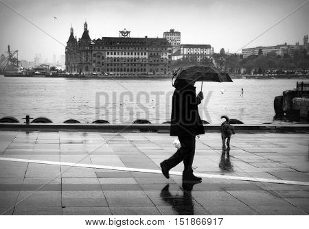 Istanbul Turkey - April 18 2014: Istanbul Kadikoy Steamboat pier and Haydarpasa train station building. People walking in the rain pier. Strait of Istanbul Kadikoy Pier ferries are the most popular form of public transport in Istanbul for.