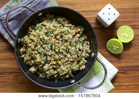 Quinoa salad with lentils and parsley in bowl photographed overhead on wood with natural light (Selective Focus Focus on the top of the salad)