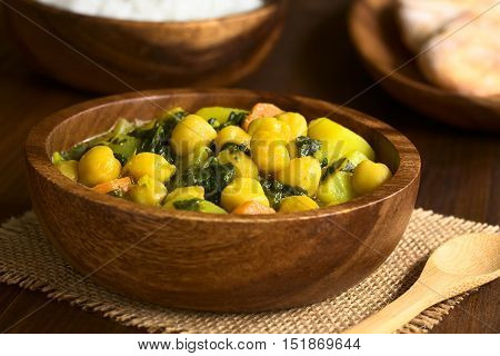 Vegan chickpea curry or chana masala with spinach potato and carrot served in wooden bowl photographed with natural light (Selective Focus Focus one third into the curry)
