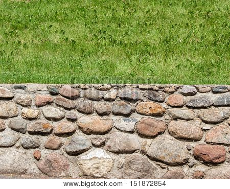 horizontal image of a two part image of the bottom half as a stone wall and top half green grass