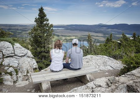 horizontal image of a woman and man sitting on a wooden bench way on top of a mountain and looking down on the beautiful landscape below in the summer time.