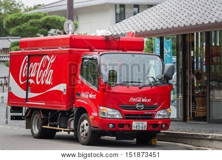 Kyoto Japan - September 16 2016: One of the red Coca-Cola delivery trucks in front of retailer in the street. Iron fence on top holds the bags full of empty recycled bottles.