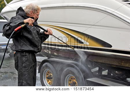 Caucasian man pressure washing hull of power boat