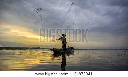 Fisherman of Bangpra Lake in action when fishing in the sunshine morning Thailand