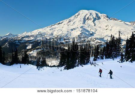 Snowshoers Descend Pinnacle Peak in The  Tatoosh Range.  Mt. Rainier National Park, Washington.