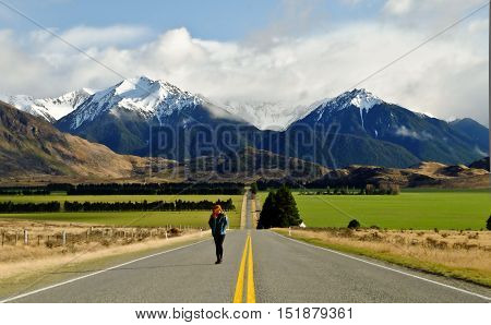 A Woman Walking the Long Road to Green Pastures. Arthurs Pass, Canterbury, Southern Alps, New Zealand