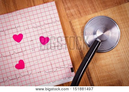 Hearts of paper and medical stethoscope lying on electrocardiogram graph ecg heart rhythm medicine and healthcare concept