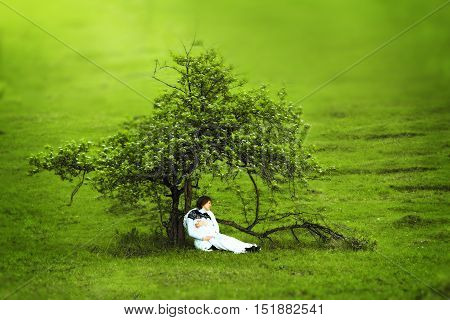 Pregnant woman sitting alone under a beautiful tree in the summer the concept of time loneliness pregnancy and expectations
